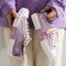 女性はロートップカソールキャンバスフラットシューズをひもで締めます - 紫